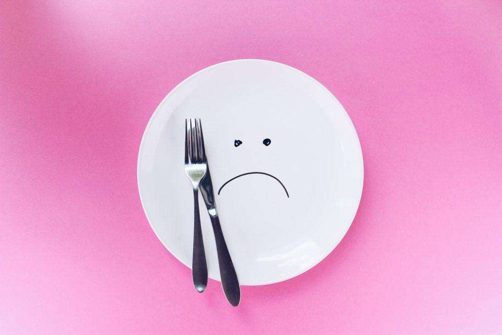 Plate with a sad face drawn on