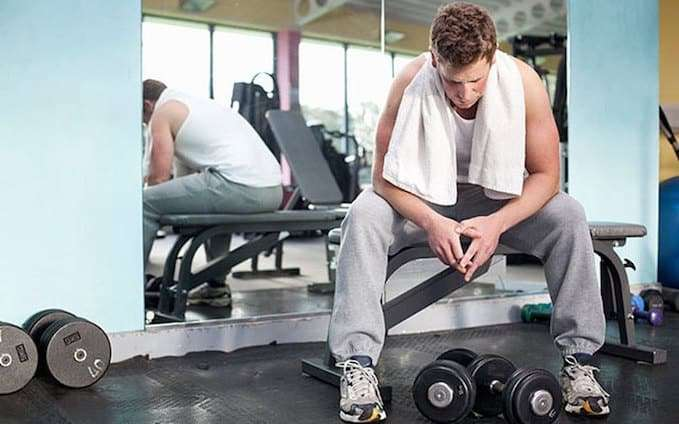 Man sitting on bench in the gym
